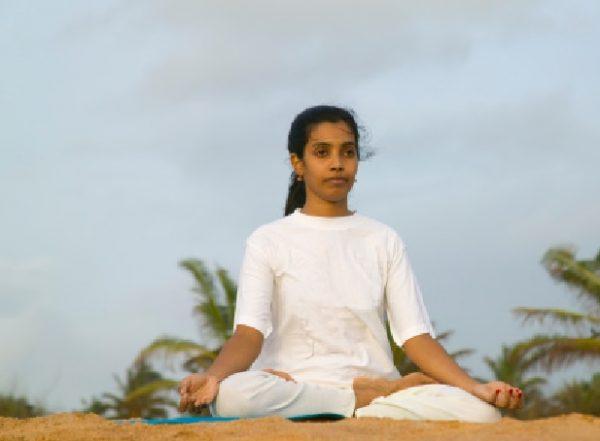 Indian girl practising yoga on beach.